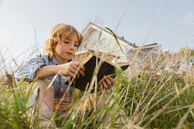 Portrait of a boy sitting on a meadow reading a book
