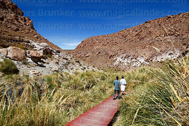 Couple walking on wooden boardwalk at Puritama thermal springs, Region II, Chile