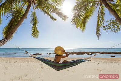 Woman relaxing on hammock under palm tree on a tropical beach, Fiji