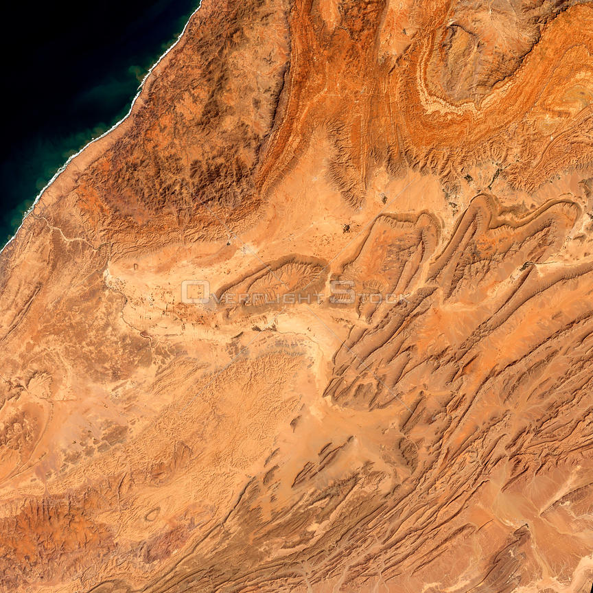 EARTH Morocco -- 19 Mar 2002 -- Sharp ridgelines and fluted-edged mesas rise out of the desert floor of southwestern Morocco.