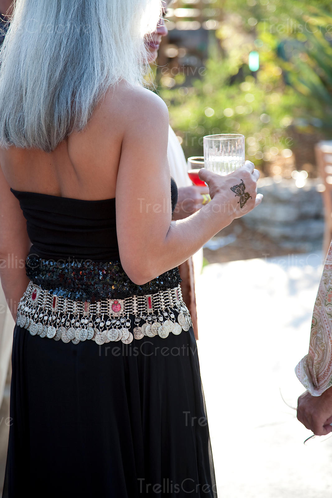 An older woman drinks wine at an outdoor party