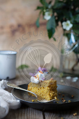 Carrot cake with cream and wild flowers