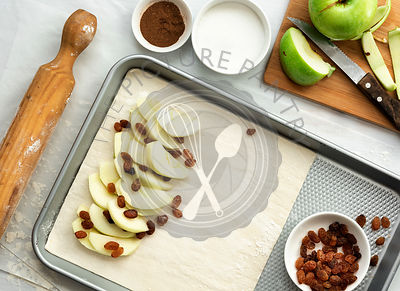 Preparation of apple strudel, apple slices and sultanas on a pastry sheet resting on a baking tray.
