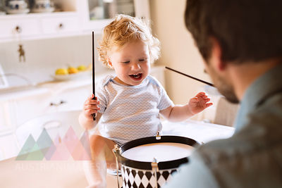 Father with happy little boy sitting on kitchen table playing drum