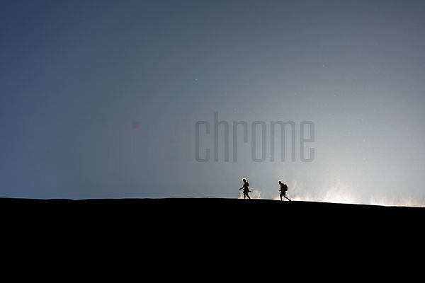 People Walking along the Top of a Dune