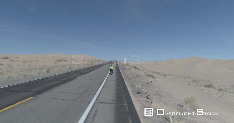 Tracking shot of cyclist going going along desert road, Brawley, California, USA.