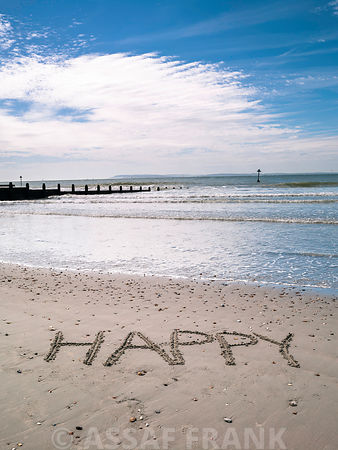 """HAPPY"" message written in smooth sand at the beach"