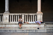 Italy - Verona - A female tourist reads from a guidebook while her male companion lies on a low wall in the Piazza dei Signori