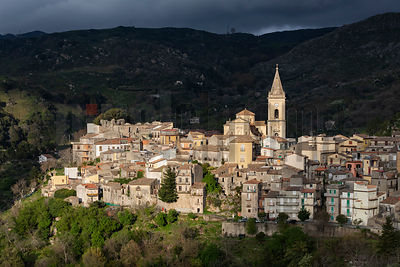 The Late Afternoon Sun Lights up the Picturesque Town of Novara di Sicilia with a Spotlight Ray in a Gap through the Fast-Mov...