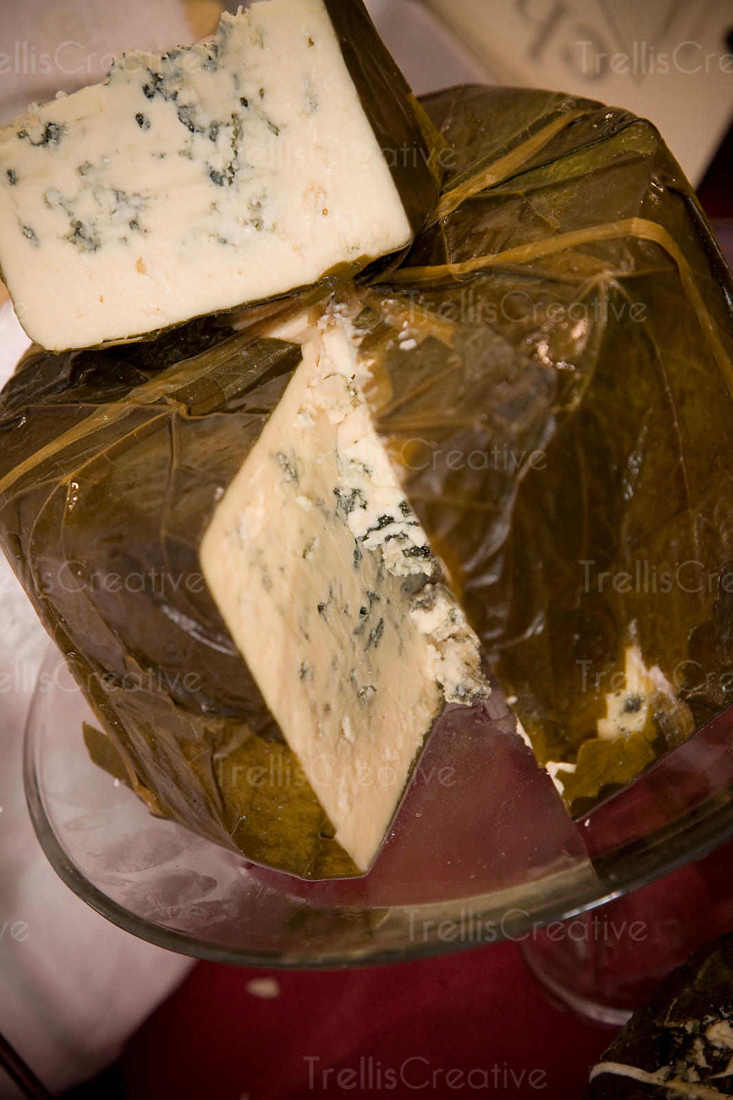 A wheel of delicious blue cheese wrapped in grape leaves