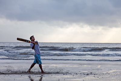 A man hits a cricket ball on Juhu Beach, Mumbai, India.