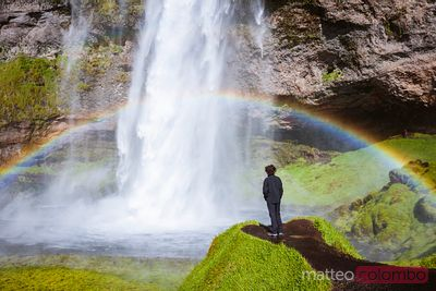 Boy standing in front of Seljalandsfoss waterfall, Iceland