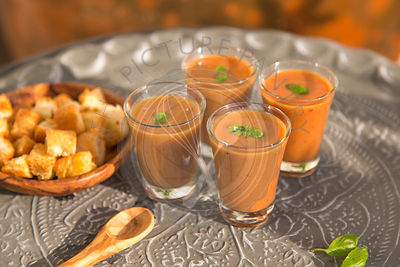 outdoors shot of tomato gazpacho or soup in glasses with basil on metal tray