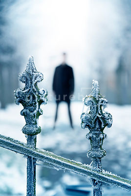 An atmospheric image of a blurred man standing behind the hoar frosted old iron gates of a church, in winter.