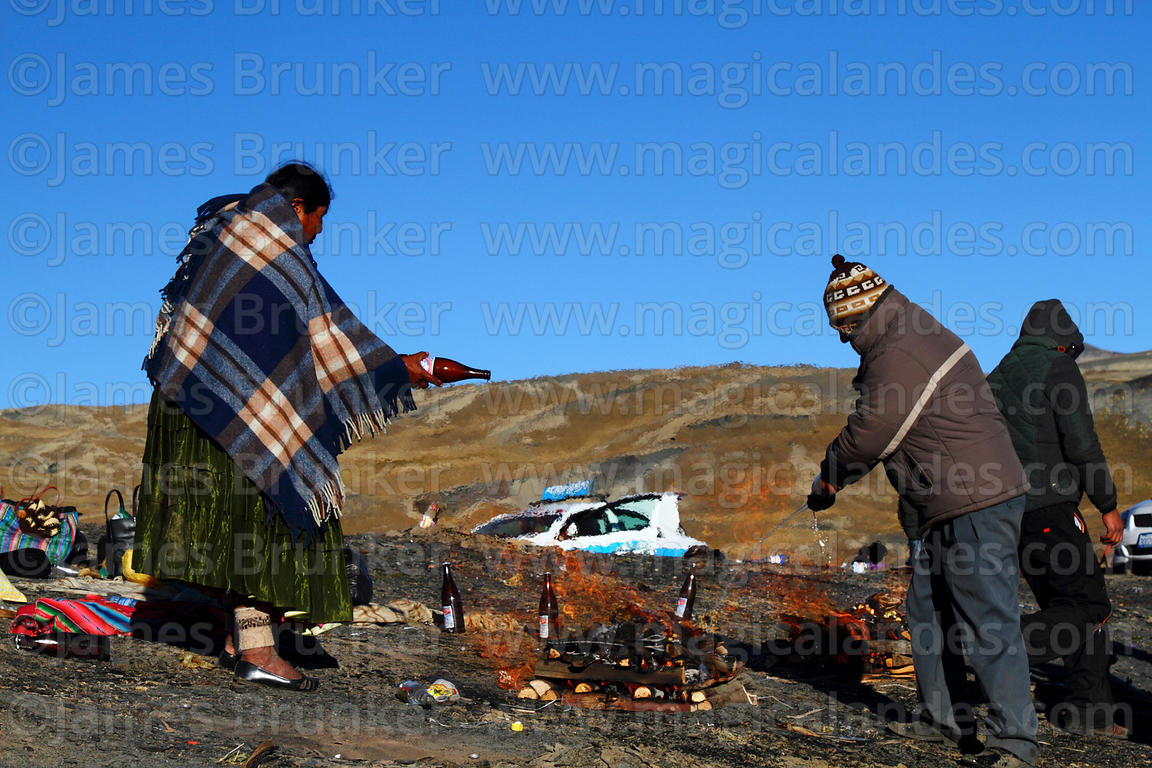 A couple pour beer on burning offerings (called k'oas) to Pachamama, La Cumbre, Cordillera Real, Bolivia