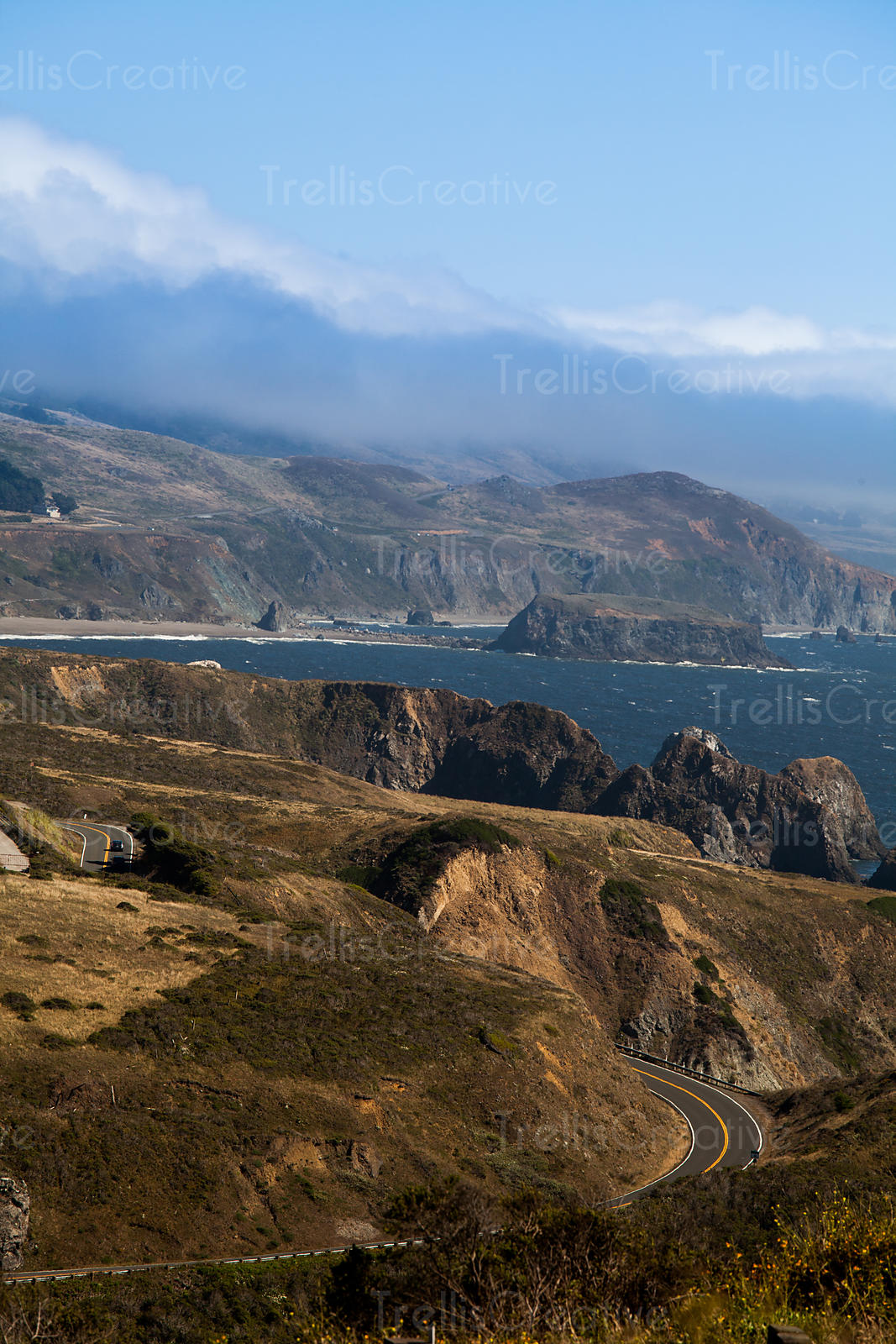 Fog lifts over the hills of the Great Highway along the Northern California coastline.