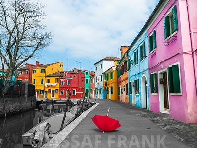Red umbrella and multi-coloured houses next to a canal, Burano, Italy