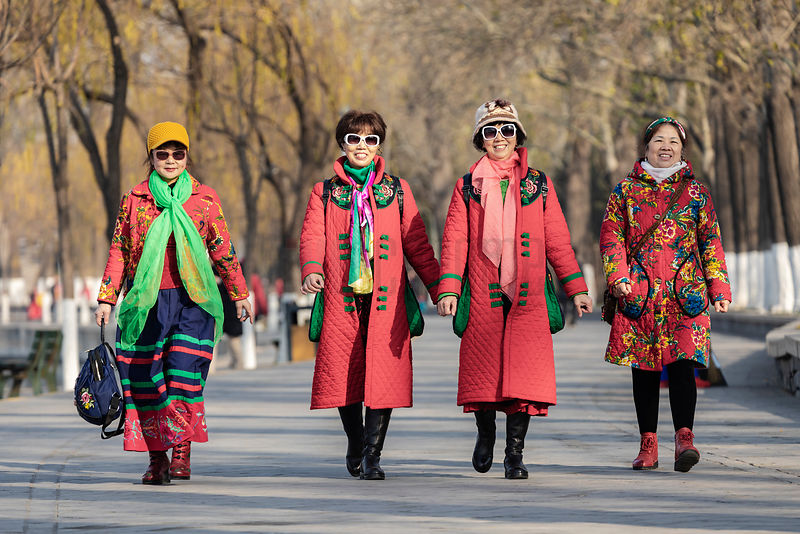 Chinese Women Dressed in Red Walking at the Old Summer Palace