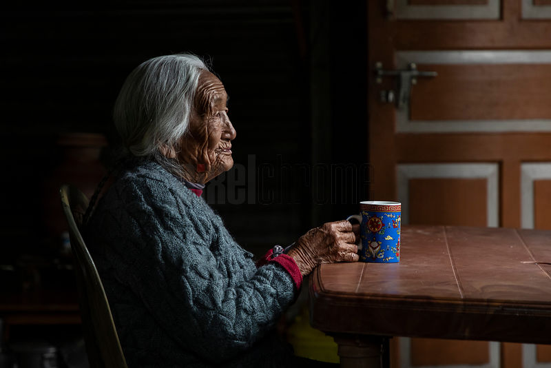 Portrait of Chindumu Lepcha (98) Sitting at the Kitchen Table Drinking a Cup of Tea