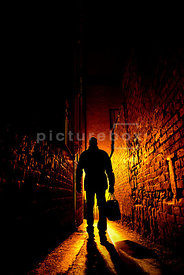An atmospheric image of the silhouette of a mystery man, with a bag, walking down an alley at night.