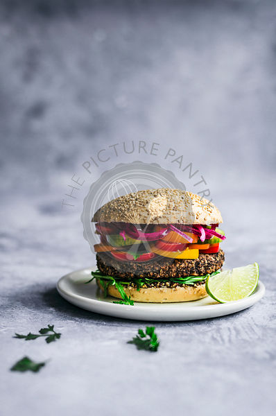 Vegan Mexican black bean and quinoa burger on sesame bun with lime and picked onions