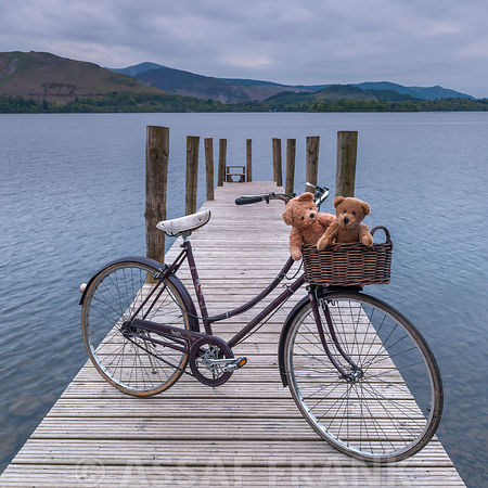 Bicycle with teddy bears on lake jetty