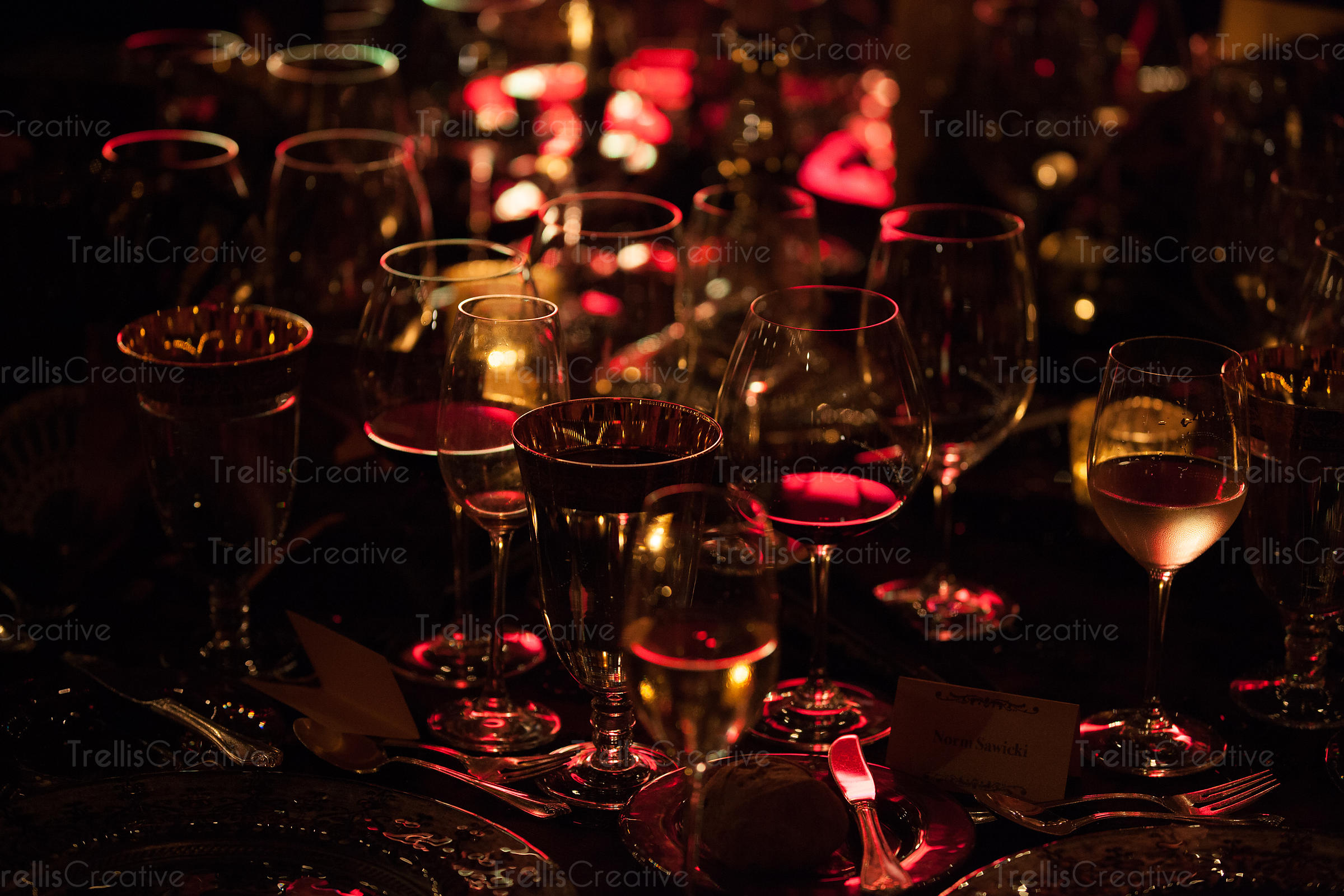 Wine glasses glow in the dim red light at a party on a table
