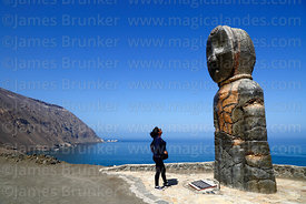 Tourist looking at modern statue of Chinchorro mummy on headland above Bahia Camarones, Region XV, Chile