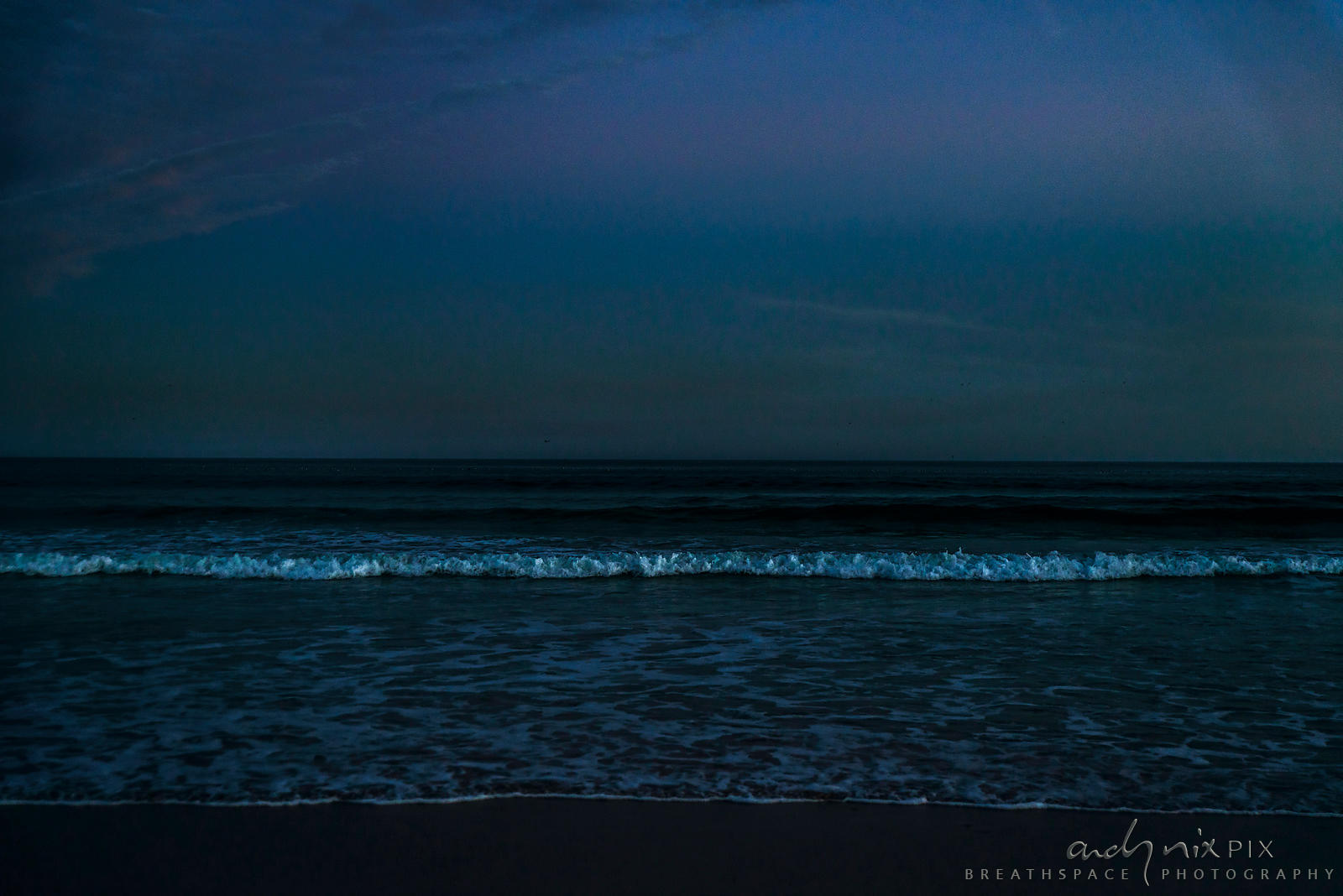 line of waves in the sea at night