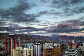 High rise buildings in Sopocachi and nearly full moon at sunset, Mt Illimani in distance, La Paz, Bolivia
