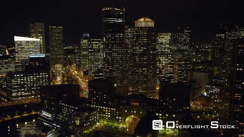 Flying over skyscrapers of downtown Boston at night.