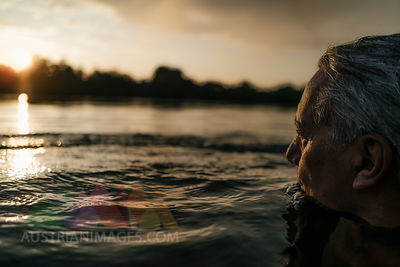 Senior man swimming in a lake at sunset