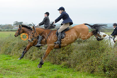 George Ward and Fiona Applewhite jumping a hedge at Sheepwash
