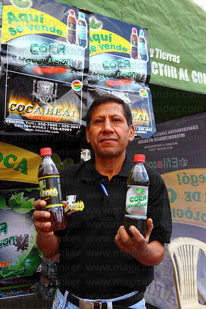 Man showing samples at a stall selling fizzy soft drinks at trade fair promoting alternative products made from coca leaves ,...