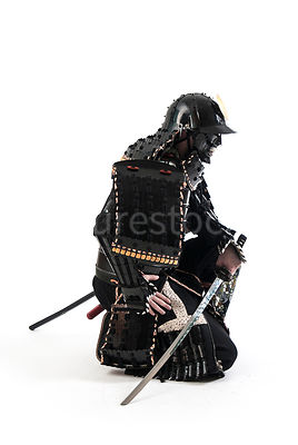 A Samurai warrior kneeling with his sword - shot from mid-level.