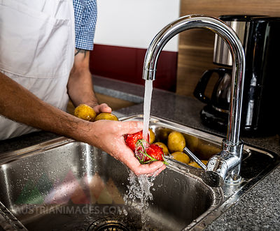 Austria, Man in kitchen washing vegetables