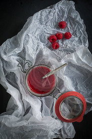 Open jar of raw raspberry & chia jam on black slate background and white paper, Top view