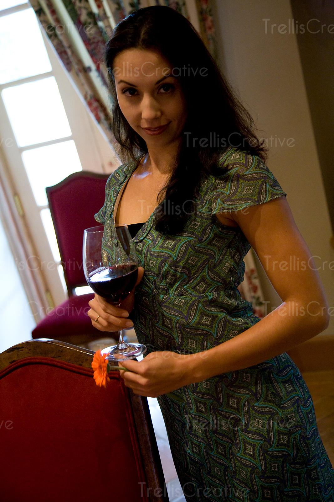 smiling young woman holding glass of wine