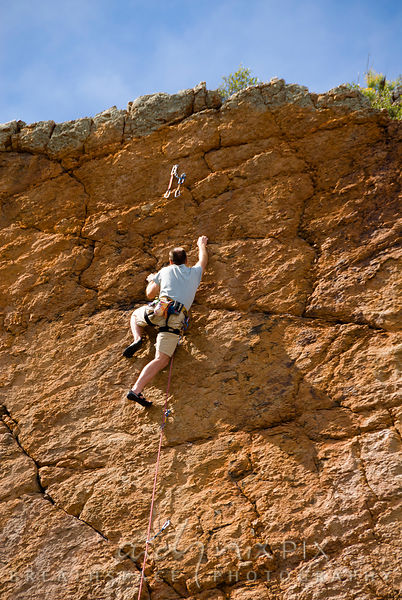 Single male rock climber on cliff face near top of route just below two quickdraws hanging from bolts in the rock