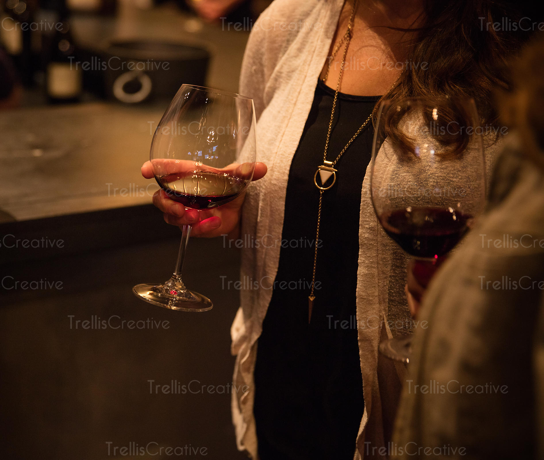 A lady holding red wine glassat an event