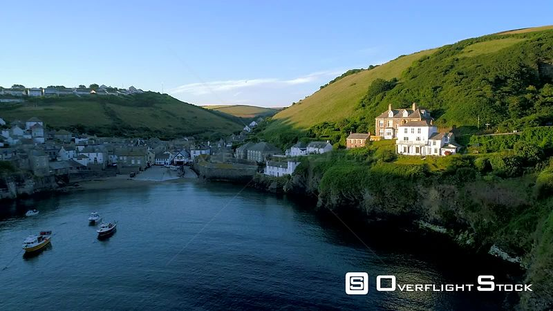 Drone flies back and rises to show the harbor of Port Isaac in Cornwall during early morning sun