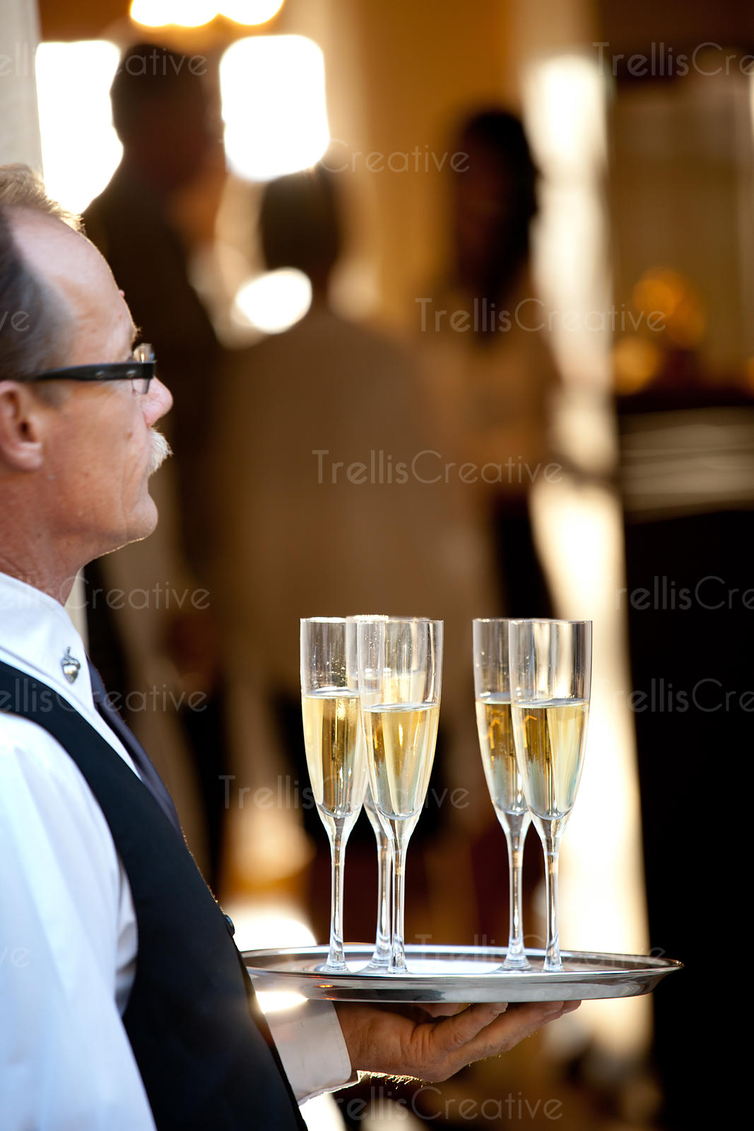 Server holding tray of glasses of champagne