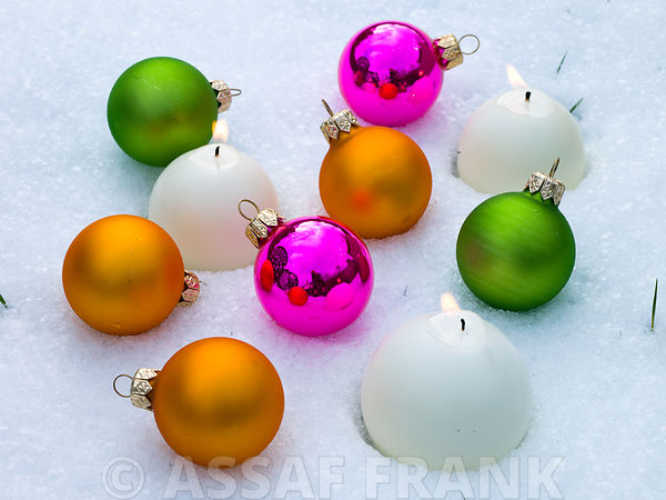 Christmas candles with baubles in snow