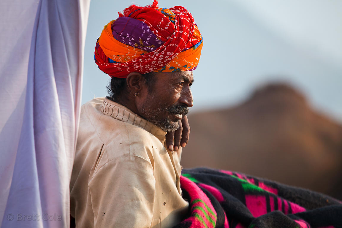 A man wakes up for the day at the 2010 Pushkar Camel Fair, Rajasthan, India