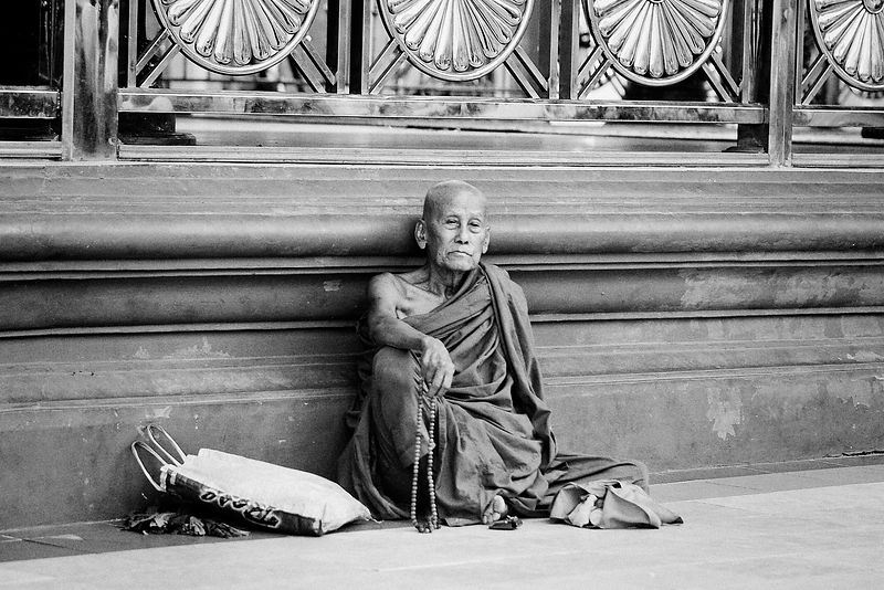 Old Buddhist monk sitting on the ground praying at Shwedagon Pagoda, Yangon