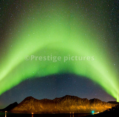 Aurora Borealis arc of light over the harbour at Gryllefjord in Arctic Norway