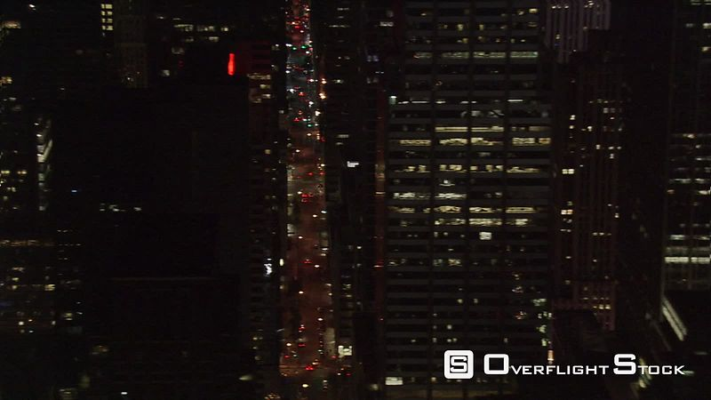 Night flight west across midtown Manhattan .