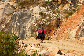 Elderly Quechua woman walking along dirt road, Torotoro National Park, Bolivia