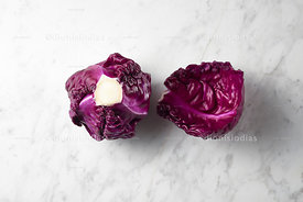 Purple cabbage with loose leaf next to marble background