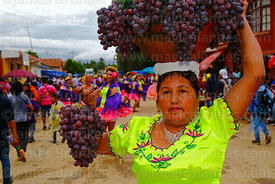 Dancer wearing traditional dress carries a ceramic bowl and grapes during Carnival parades, San Lorenzo, Tarija Department, B...